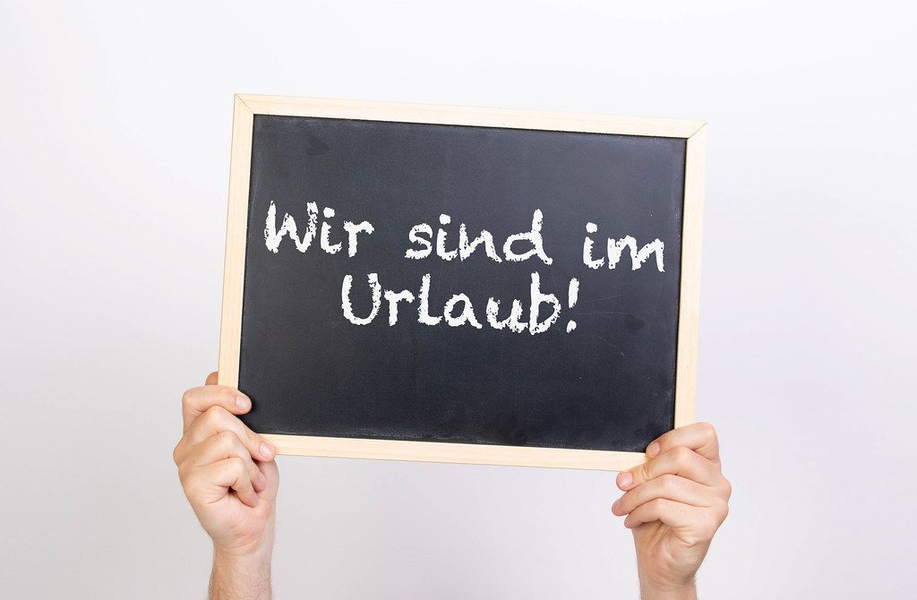 Hands holding blackboard with text Wir sing im Urlaub!