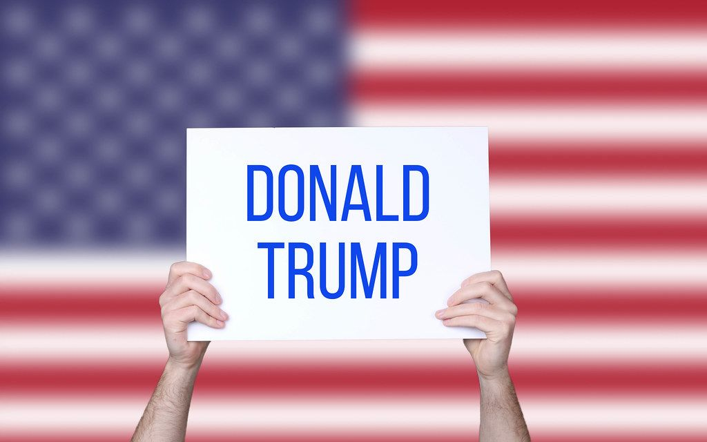 Hands holding board with Donald Trump text with USA flag background