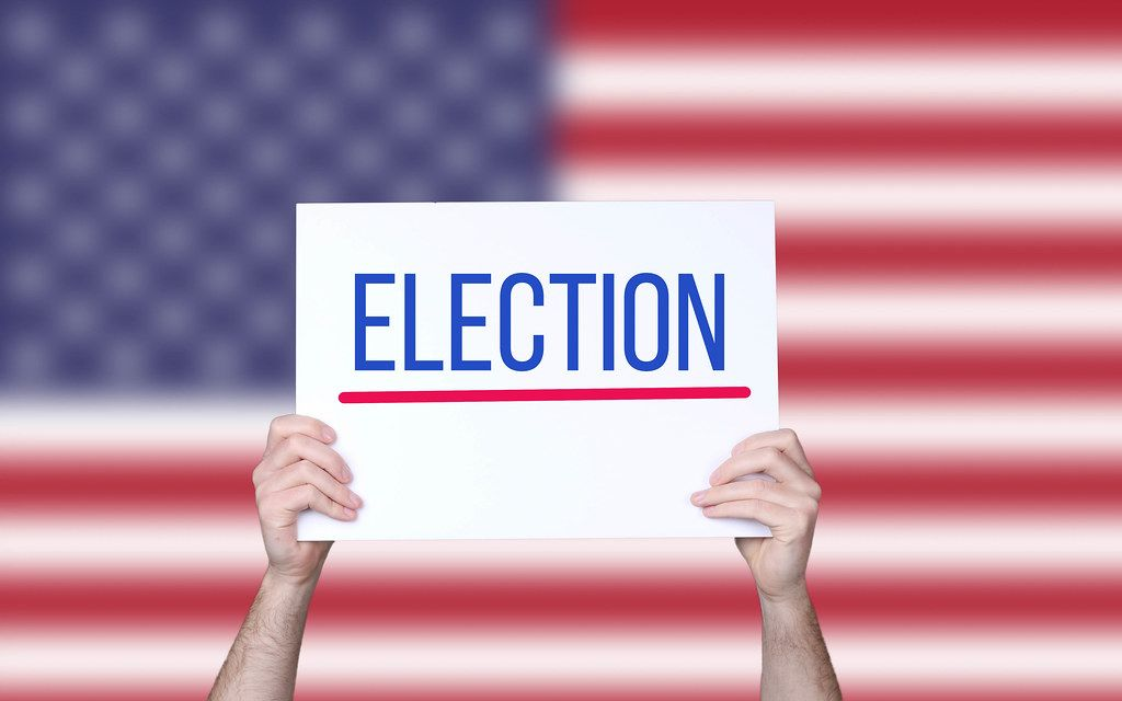 Hands holding board with Election text with USA flag background