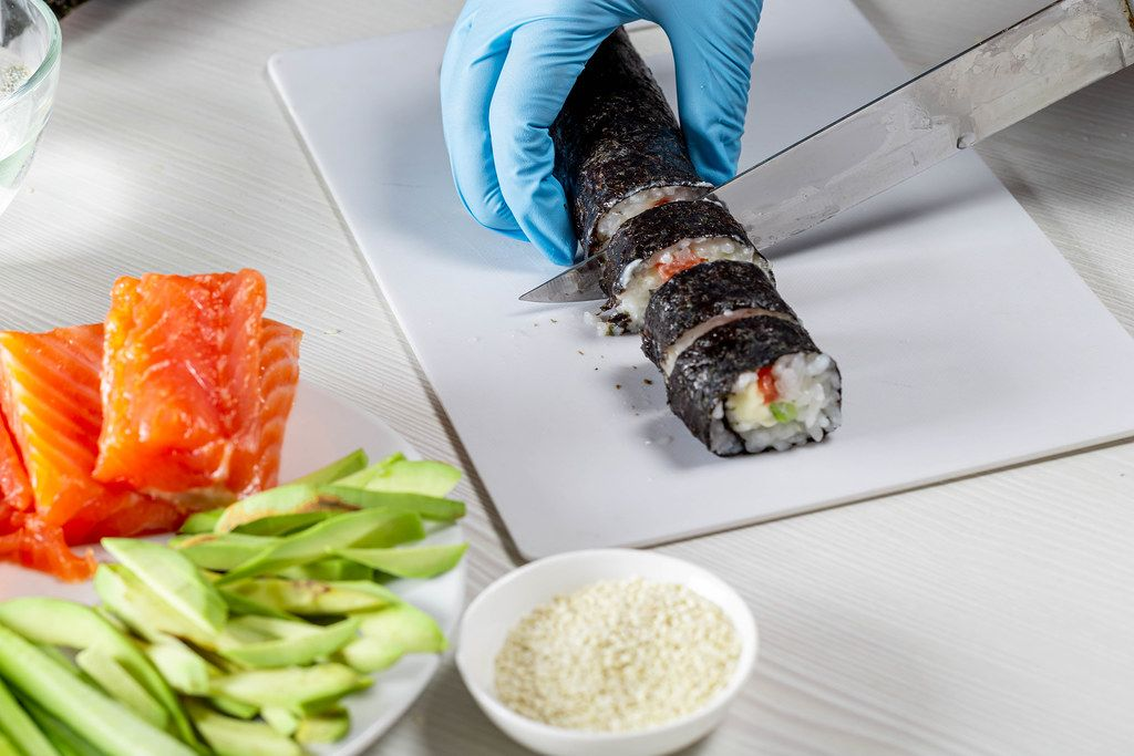Hands in disposable gloves cutting sushi rolls on a cooking board (Flip 2019)