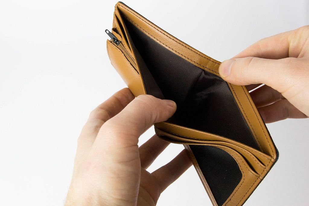 Hands opening an empty wallet on white background