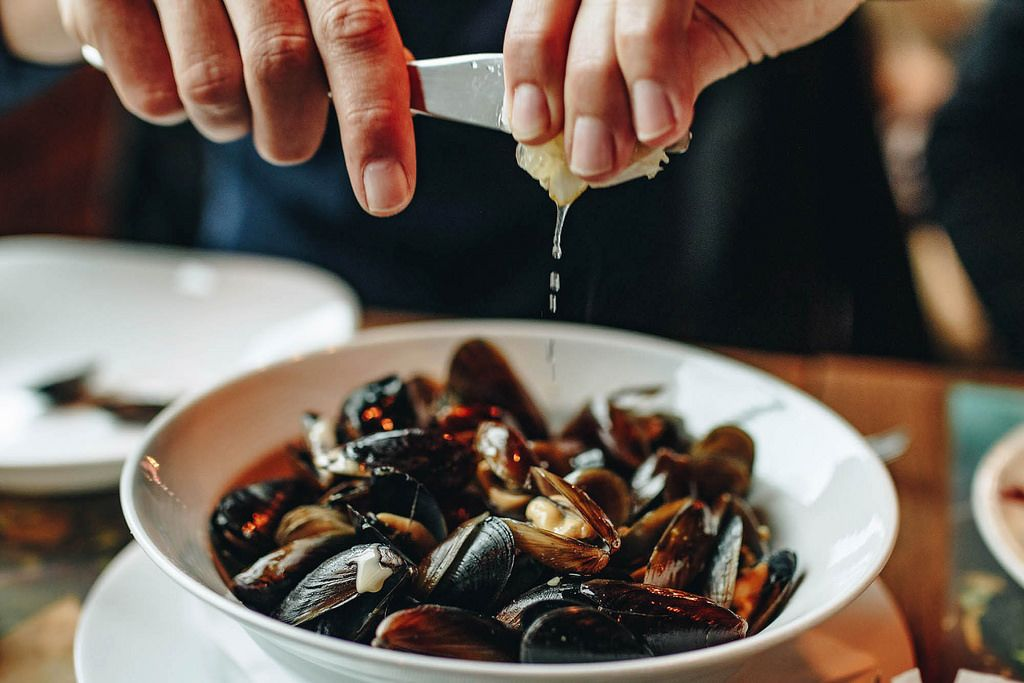 Hands squeezing lemon over plate with mussels.