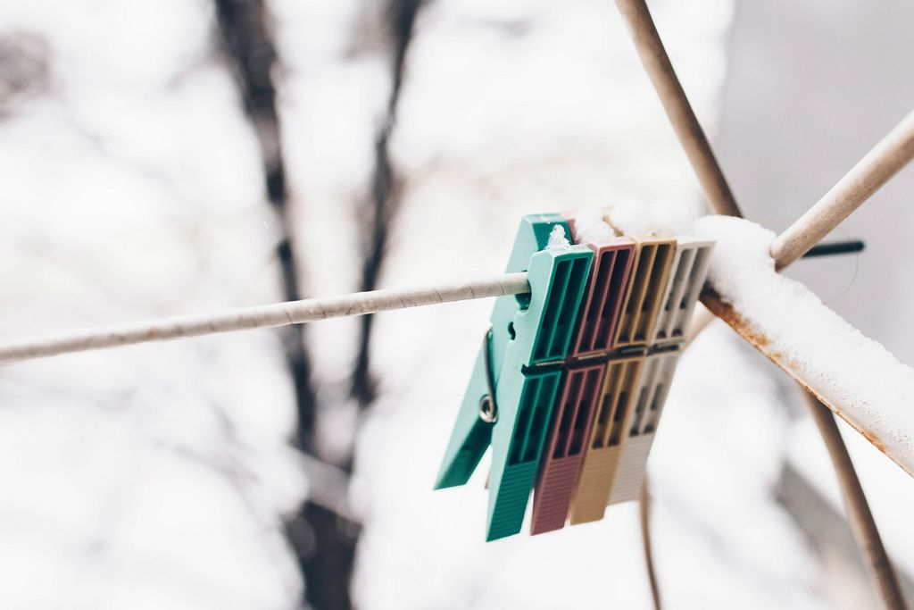 Hanging clothespins on snowy background.