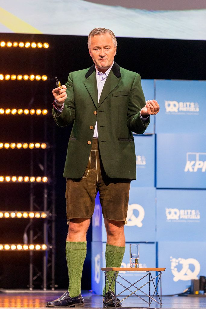 Hannes Ametsreiter von Vodafone Deutschland hält eine Rede in Lederhosen und gestikuliert auf der Bühne von Gründerkonferenz Bits & Pretzels in München