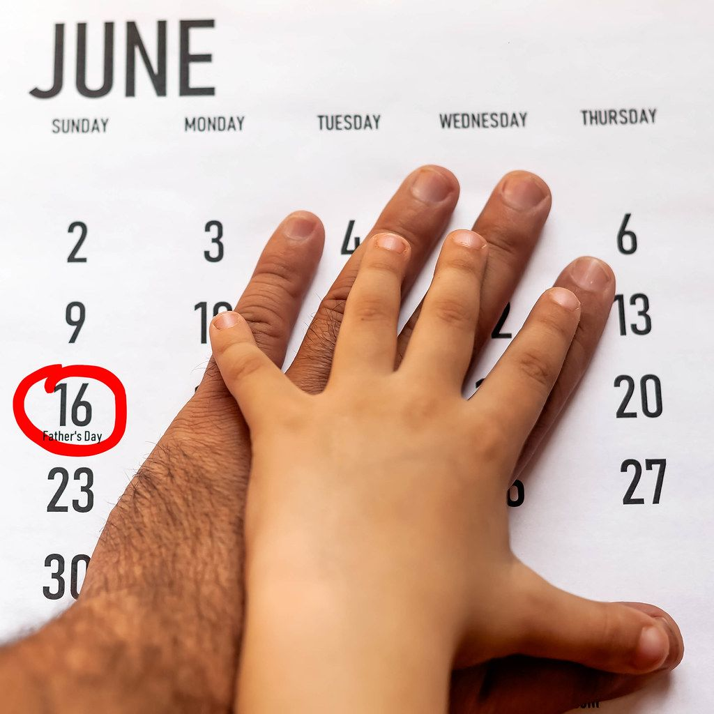 Happy Father's Day concept. 16 June 2019. Father and his son putting their hands on the calendar.