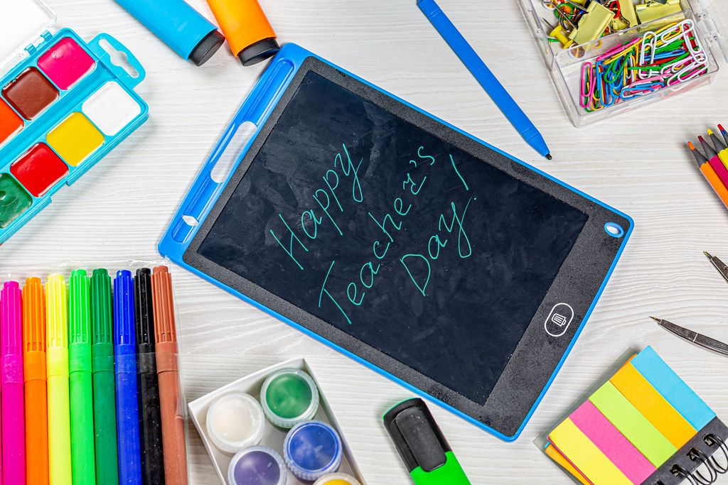 Happy Teacher's Day inscription with markers, pencils, paper clips, paints and compasses on a white wooden table. Top view