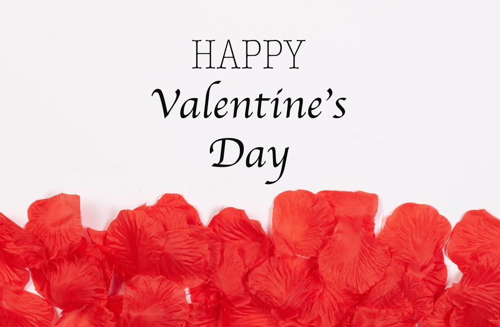 Happy Valentines day with red rose petals