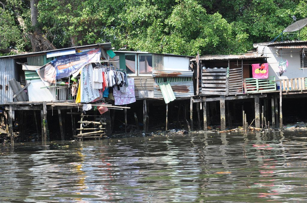 Häuser auf Stelzen im verschmutzten Wasser - Thailand
