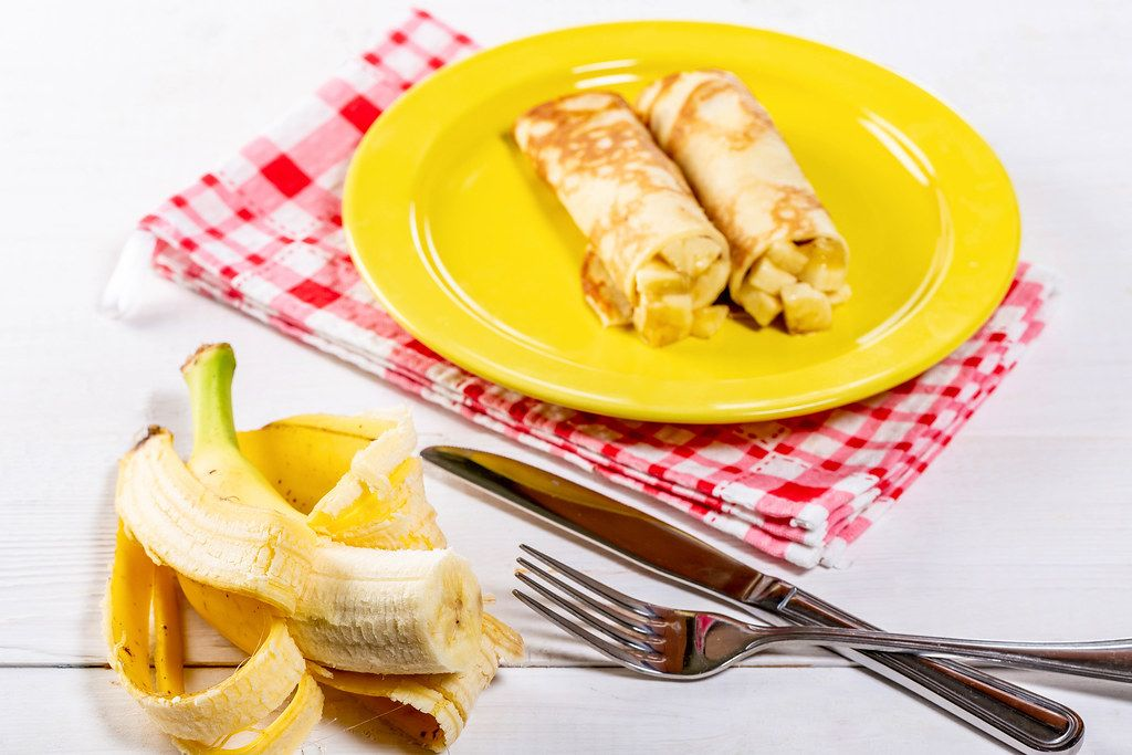Hausgemachte Pfannkuchen mit Banane, Besteck und rotem Geschirrtuch auf einem weißen Holztisch