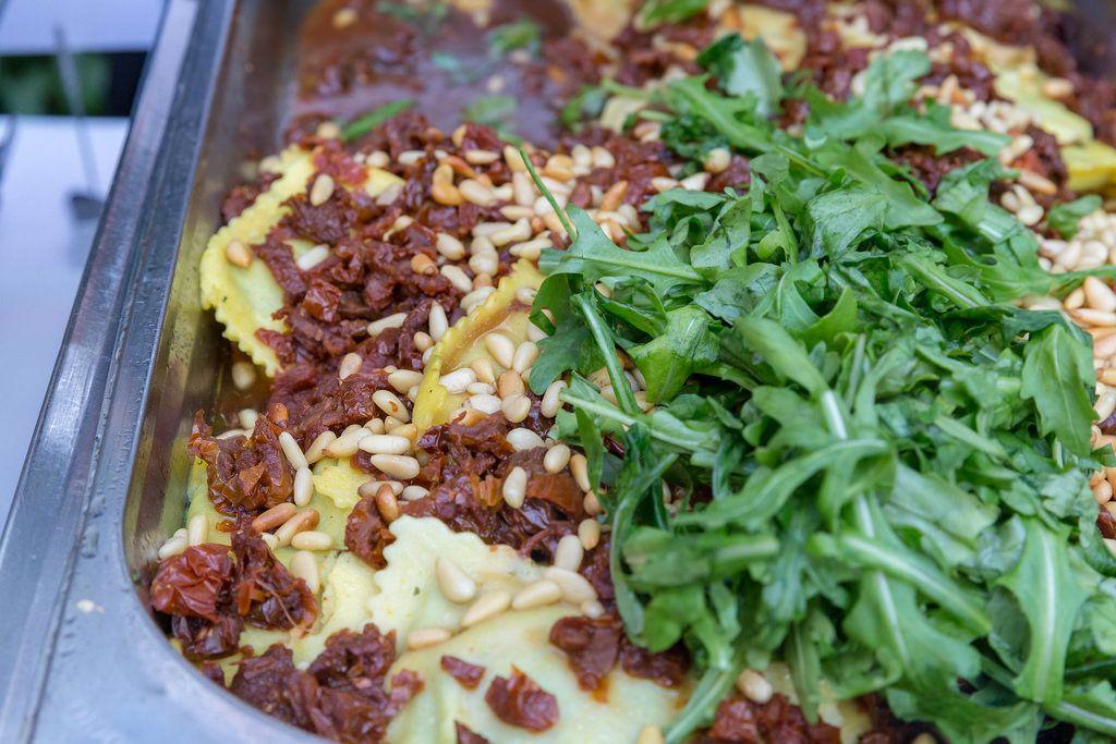 Hausgemachte Ravioli mit Spinat gefüllt, dazu getrocknete Tomaten, Pinienkerne und Rucola