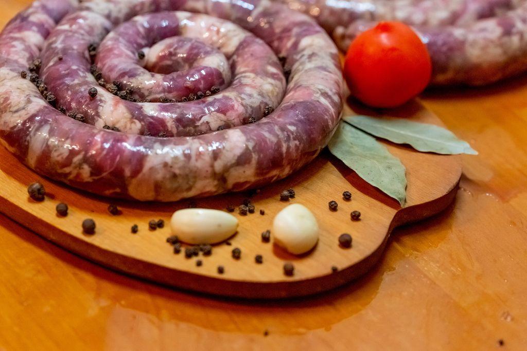 Hausgemachte, ungekochte Wurstschnecken liegt neben Tomate und Lorbeerblättern
