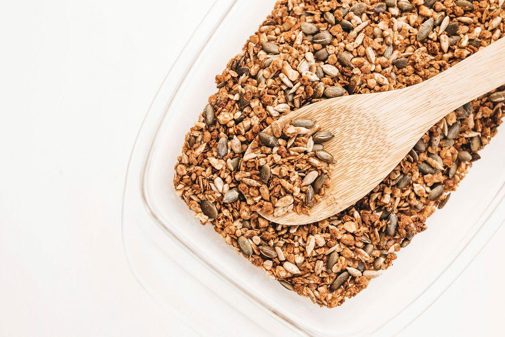 Hausgemachtes Granola aus Kernen, Samen und Nüssen mit Holzlöffel in weißer Schüssel auf weißem Hintergrund