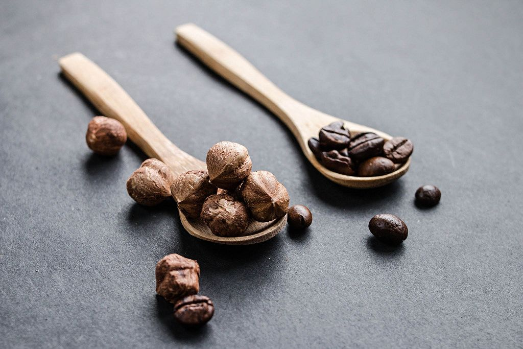 Hazelnuts and coffe beans in wooden spoons