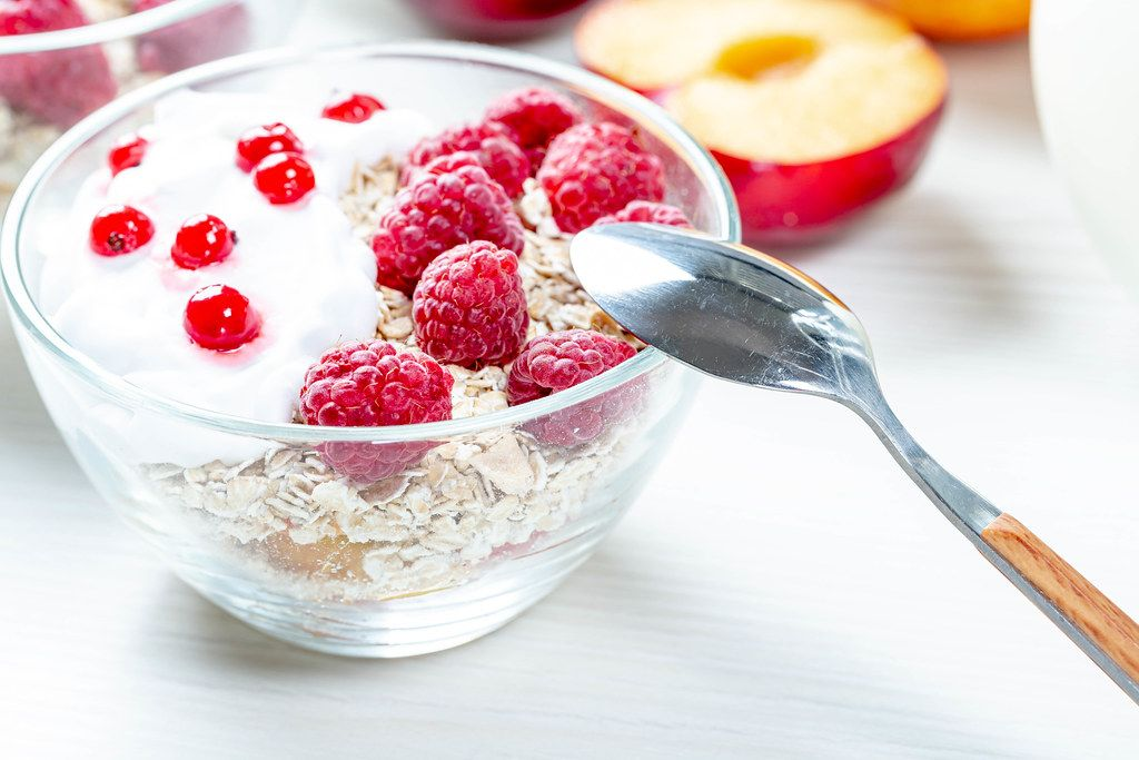 Healthy breakfast. Fresh muesli with berries in glass bowl with spoon