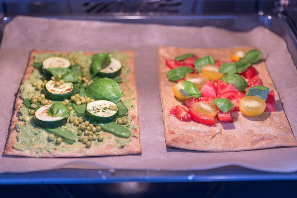 Healthy Food - two vegan pizzas with healthy toppings in the oven