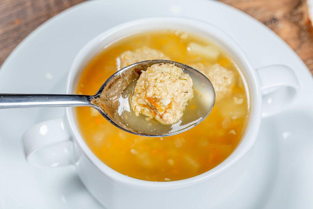 Heiße Suppe mit Fleischbällchen auf einem Löffel
