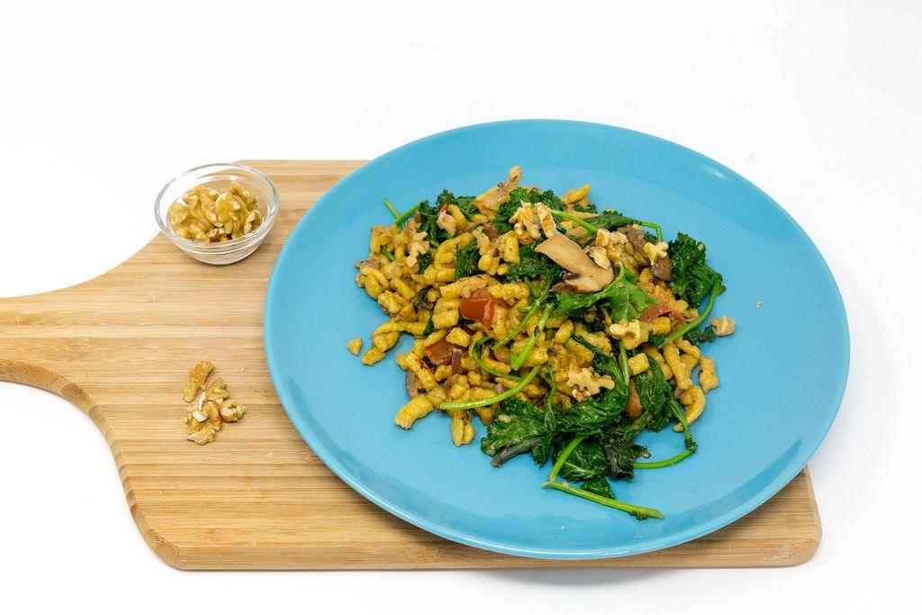 Hello Fresh - Herbstliche Grünkohl-Spätzle-Pfanne in cremiger Soße mit gerösteten Walnüssen auf einem blauen Teller auf einem Holzbrett auf weißem Hintergrund