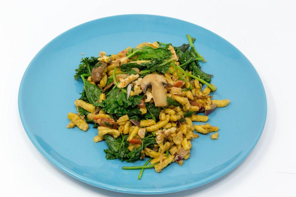 Herbst - Spätzle mit Grünkohl, Pilzen, Tomaten und gerösteten Walnüssen in cremiger Soße auf einem blauen Teller