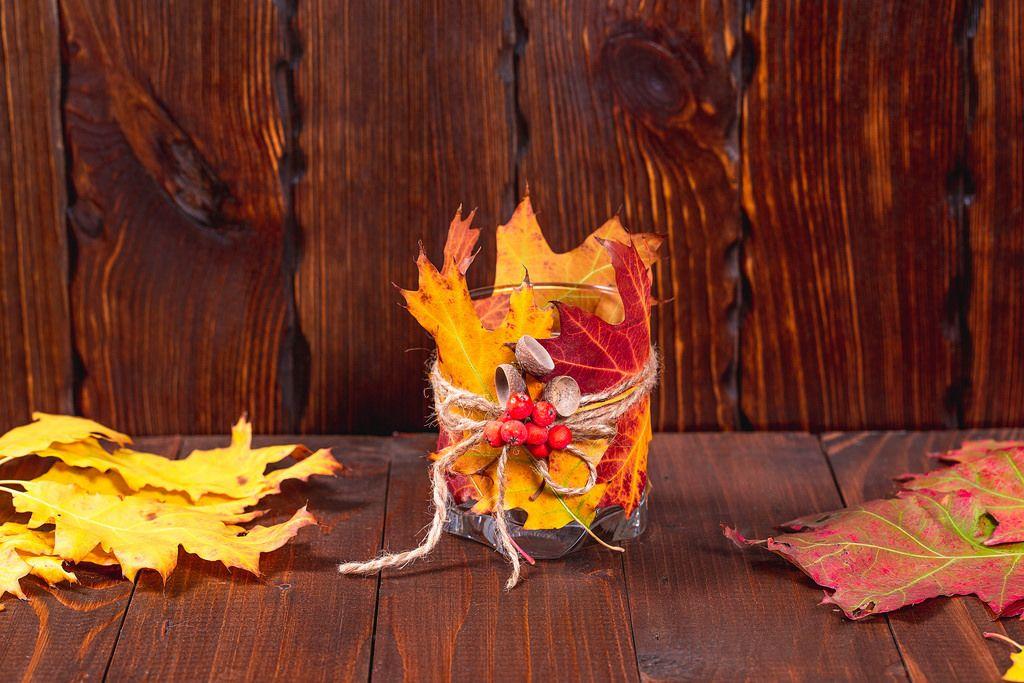 Herbstdekorationen  - Kerzenglas mit Laub und Eicheln geschmückt auf Holz-Hintergrund