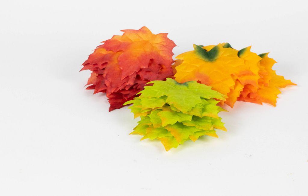 Herbstfarben Orange, Rot und Grün dargestellt mit abgefallenen Ahornblättern