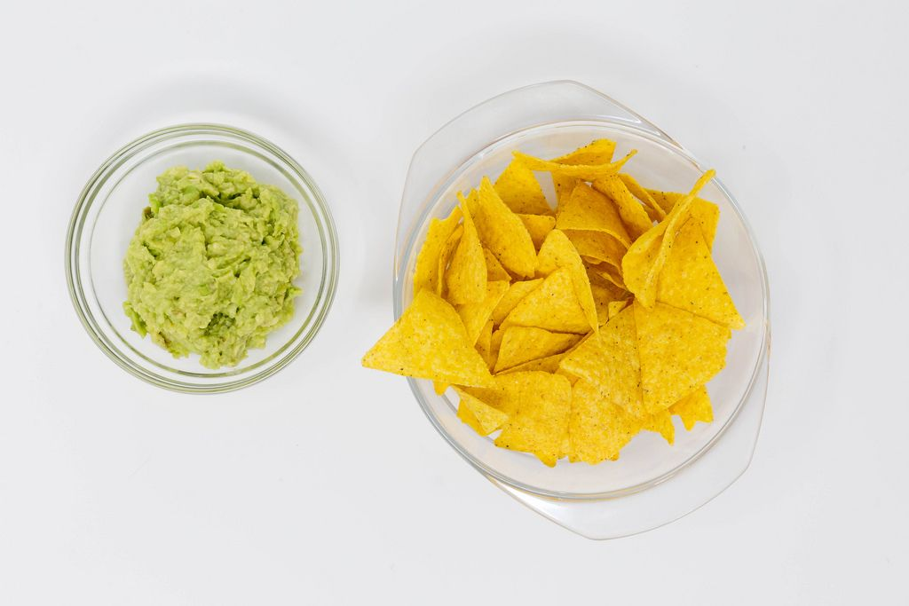 High angle shot of nachos with guacamole dip