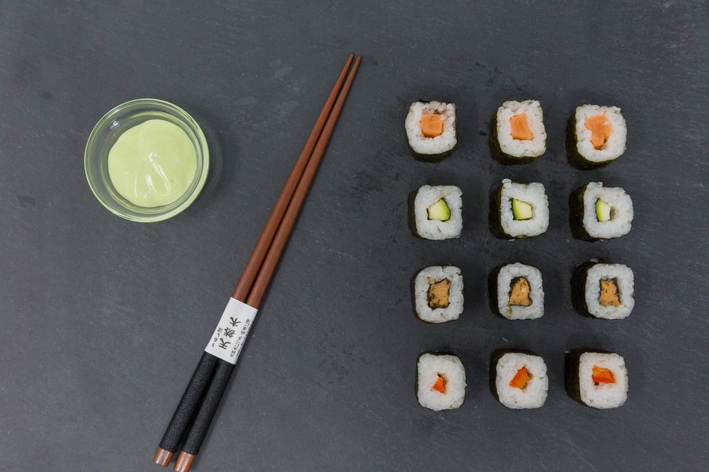 High Angle Shot of traditional japanese Chopsticks with Sushi and Wasabi Dip