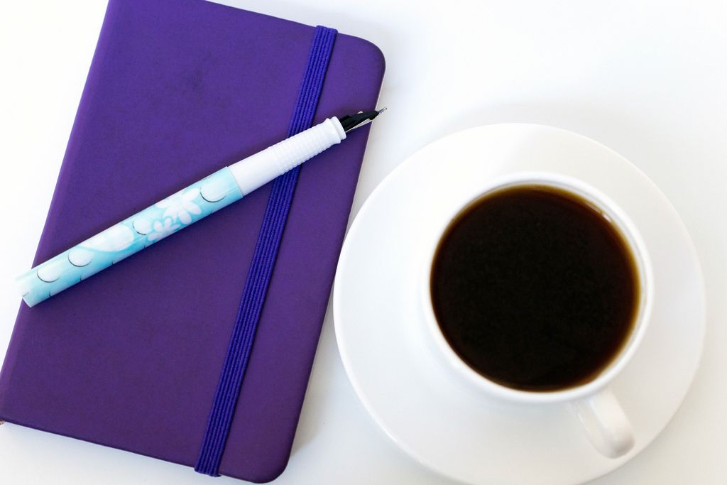 High Angle View Of The Coffee and Notebook With Pen