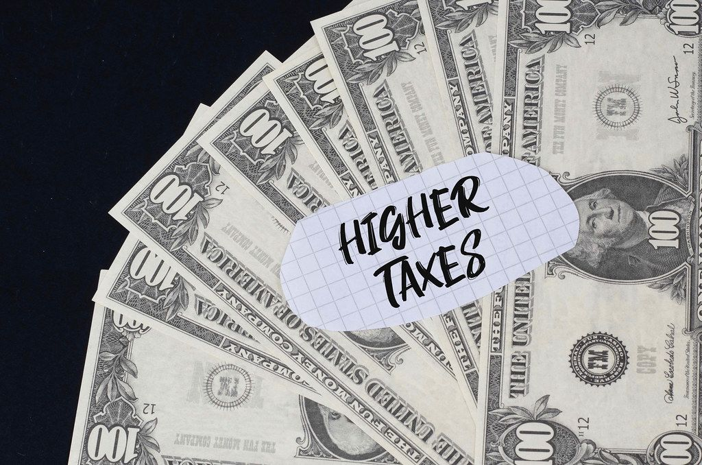 Higher Taxes text and dollar banknotes