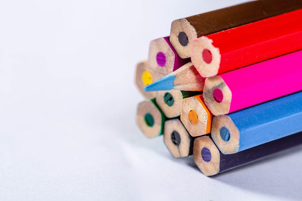 Hinteres Ende von Buntstiften in verschiedenen Farben mit einem umgedrehten Farbstift auf weißem Untergrund