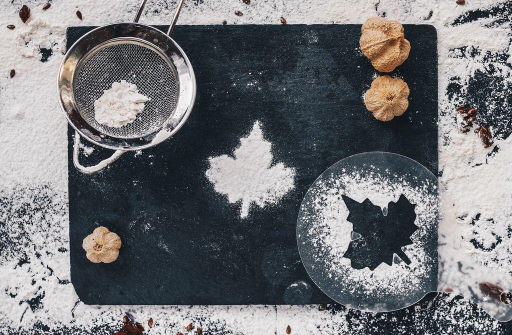 Hintergrund passend zum Kochen mit verstreutem Mehl in Blatt-Form auf einem schwarzen Küchentisch. Von oben fotografiert