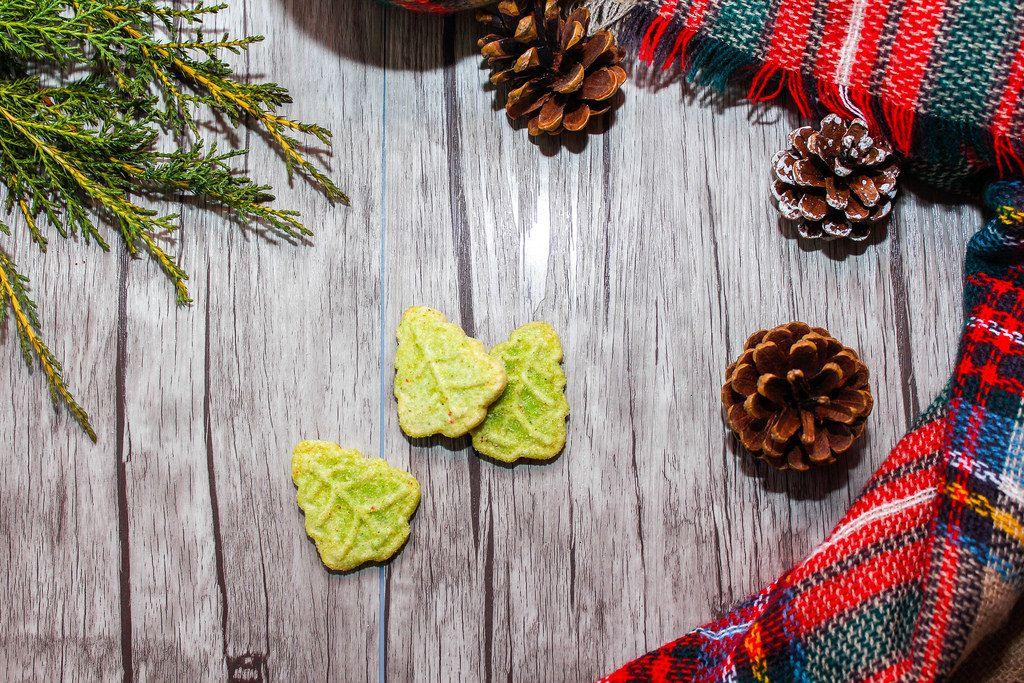 Hintergrund passend zur Festzeit mit Keksen in Weihnachtsbaum-Form, Kiefernzapfen und Ast