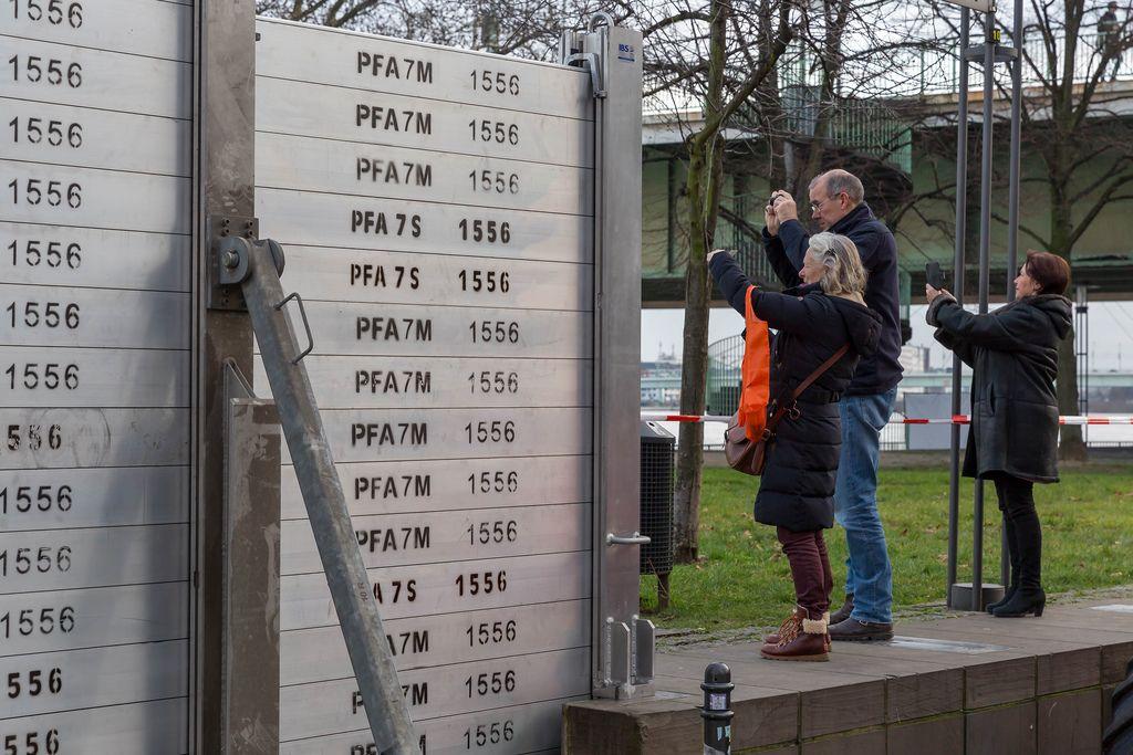 Hochwasserbarrieren und Spaziergänger die den Rhein fotografieren