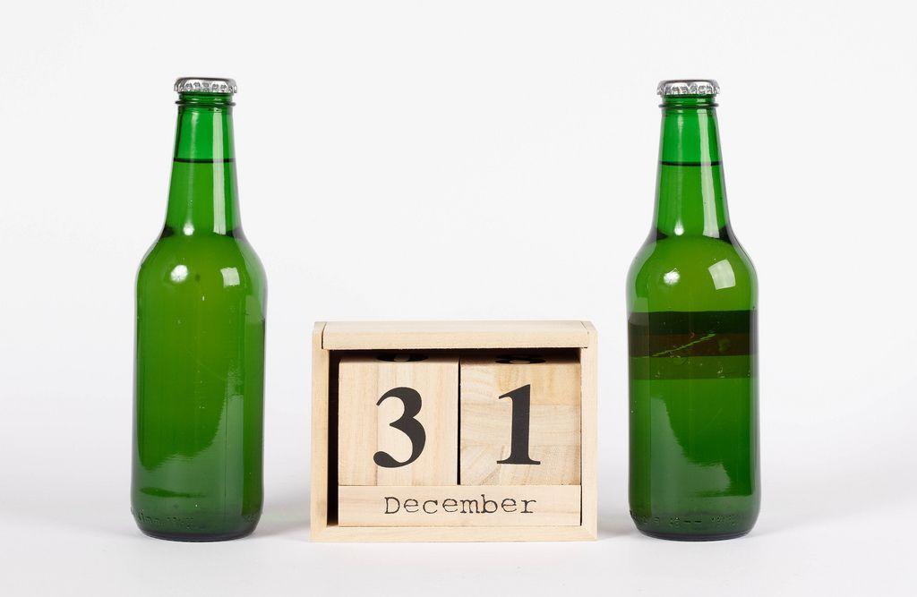 Holzkalender zeigt den 31. Dezember zwischen zwei Bierflaschen vor weißem Hintergrund