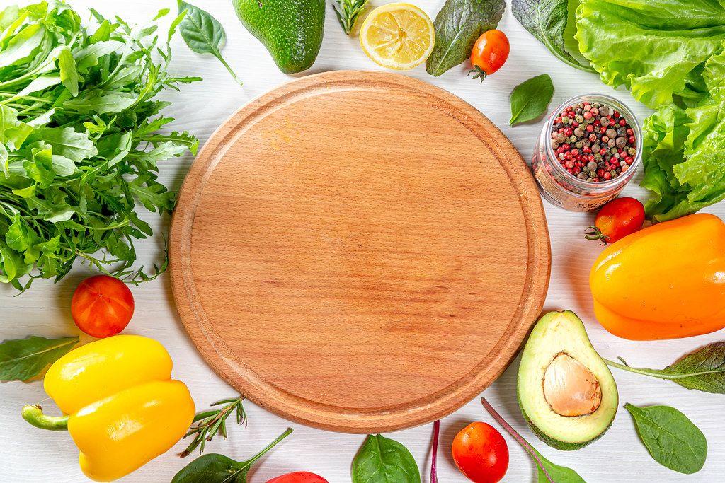 Holzküchenbrett, umgeben von Gemüse und bunten Salatzutaten