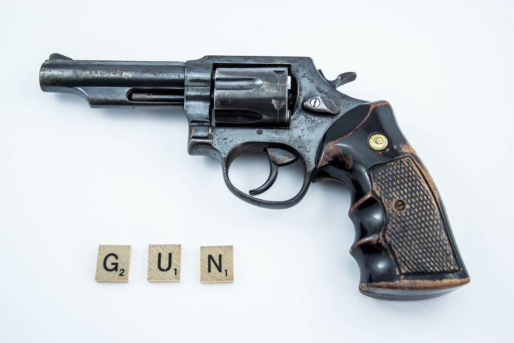 Holzplättchen mit Buchstaben bilden das Wort GUN neben Waffe auf weiße Hintergrund