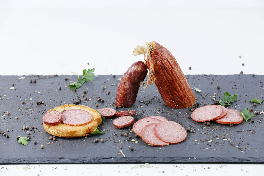Homemade salami and sausage, black background