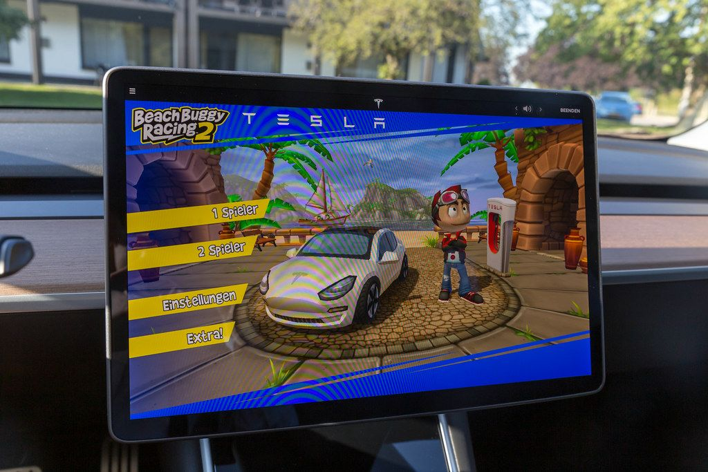 Homescreen of Beach Buggy Racing 2 for two players on the Tesla Model 3 Display, in front of a Supercharger station