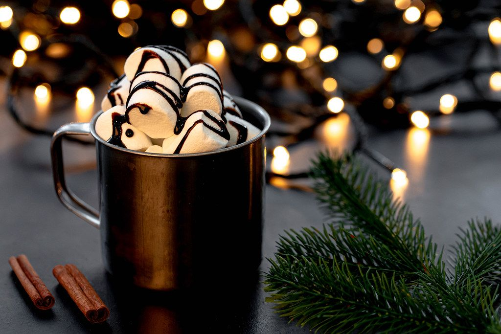 Hot chocolate with marshmallows on a Christmas background with bokeh and Christmas tree branches (Flip 2019)
