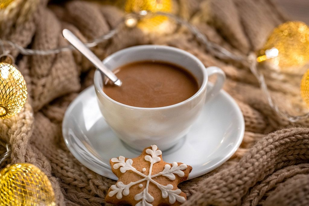 Hot coffee with gingerbread on the background of a knitted scarf and Christmas garland