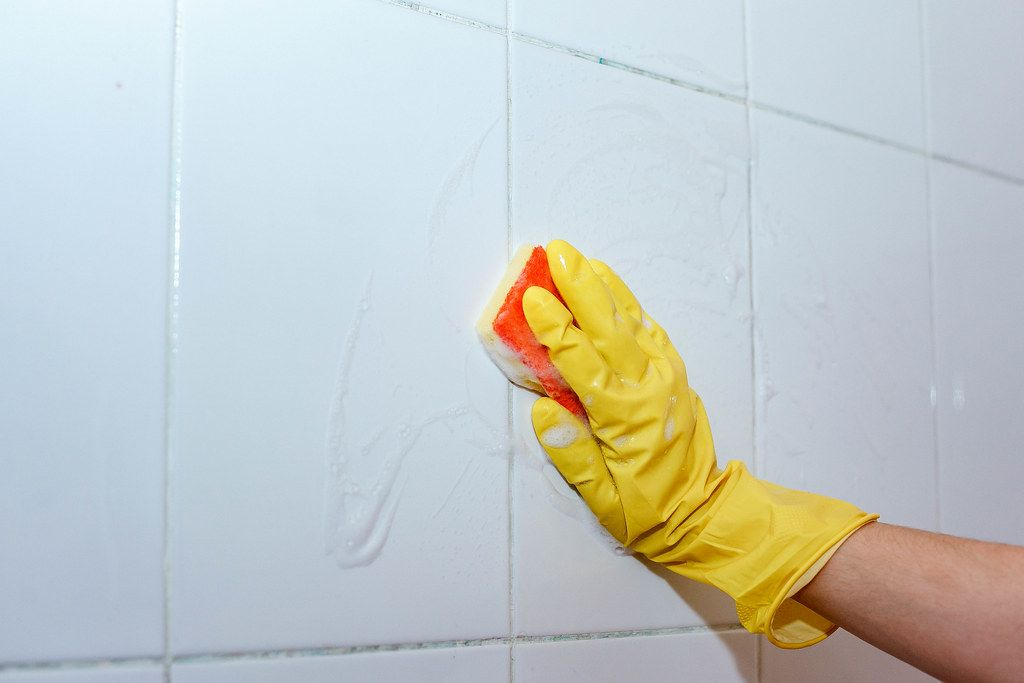 Housemaid cleaning a bathroom tiles