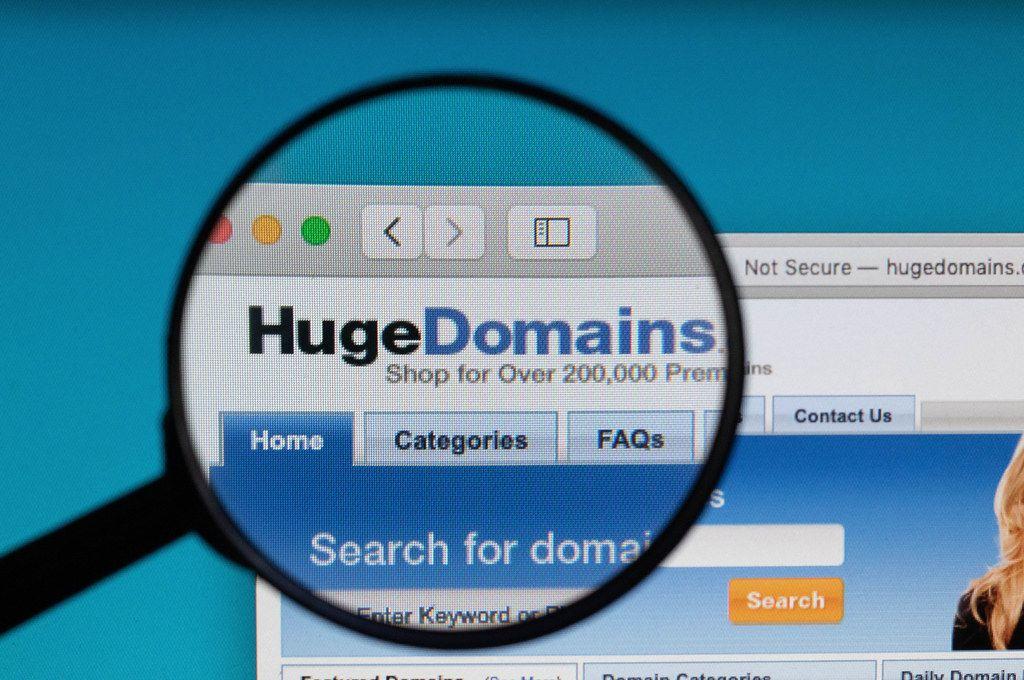HugeDomains logo under magnifying glass