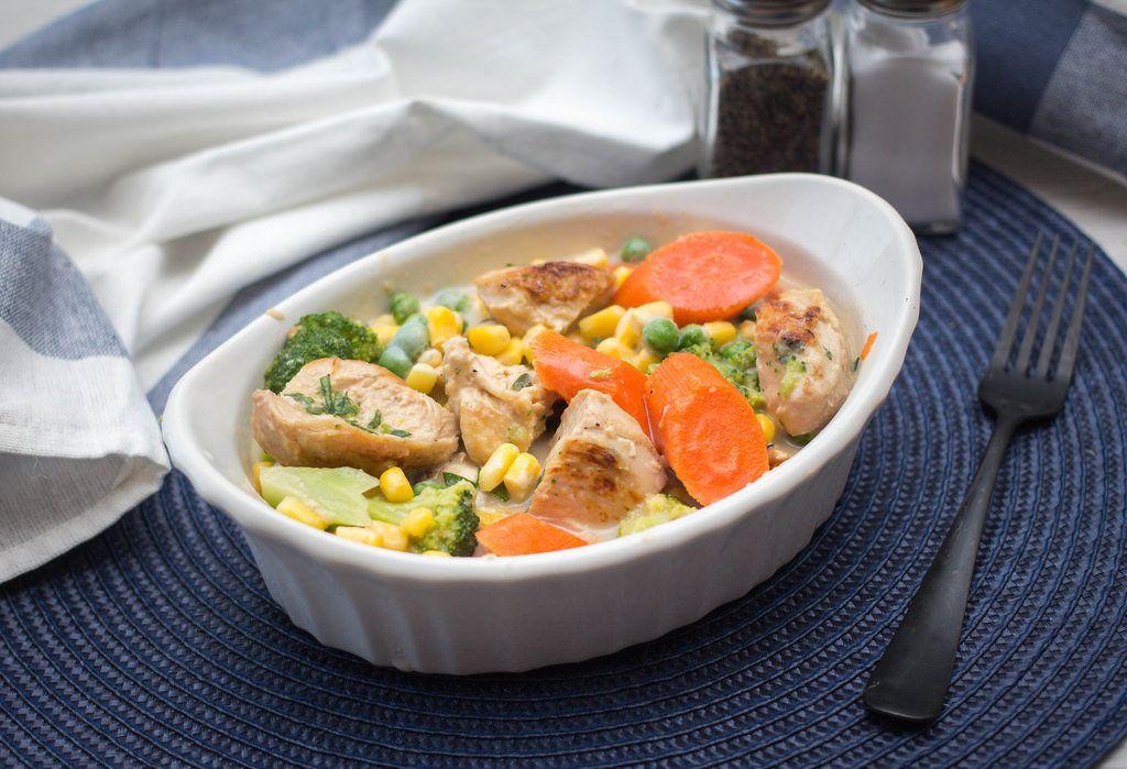 Hühnchen Kasserolle mit Karotten, Mais, Brokkoli und Erbsen in weißer Porzellanschale auf blauem Tischset mit Salz und Pfeffer im Hintergrund