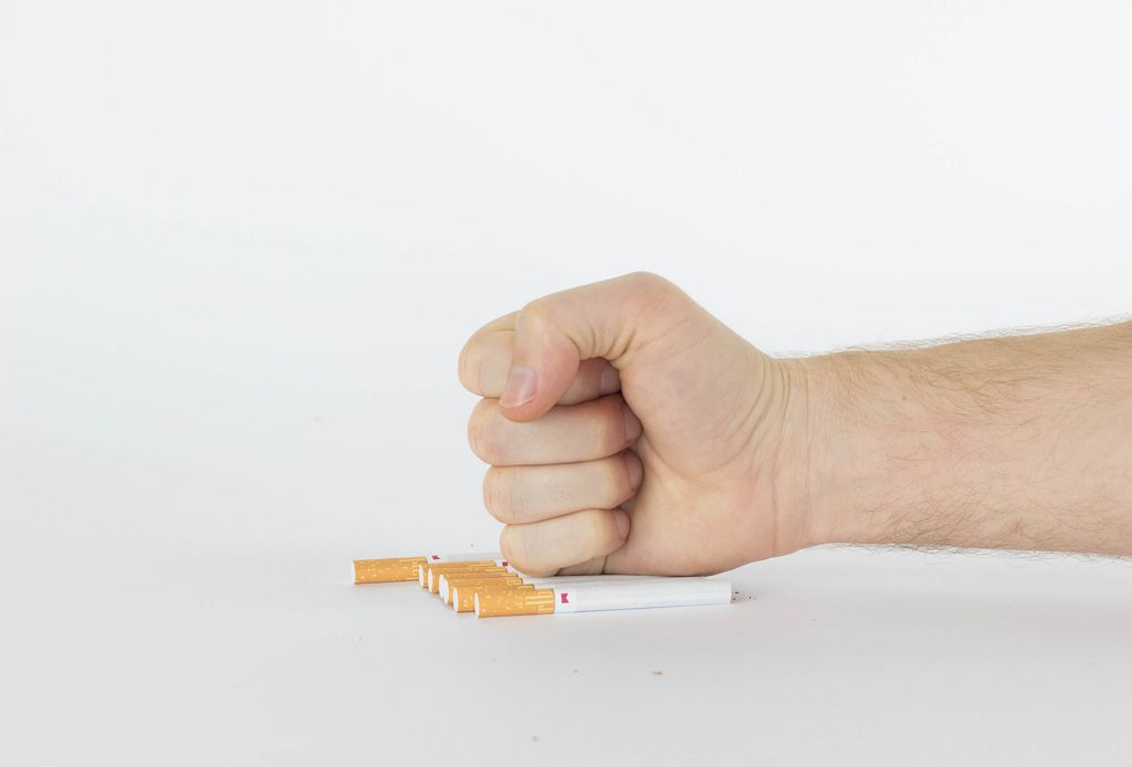 Human hand breaking cigarettes