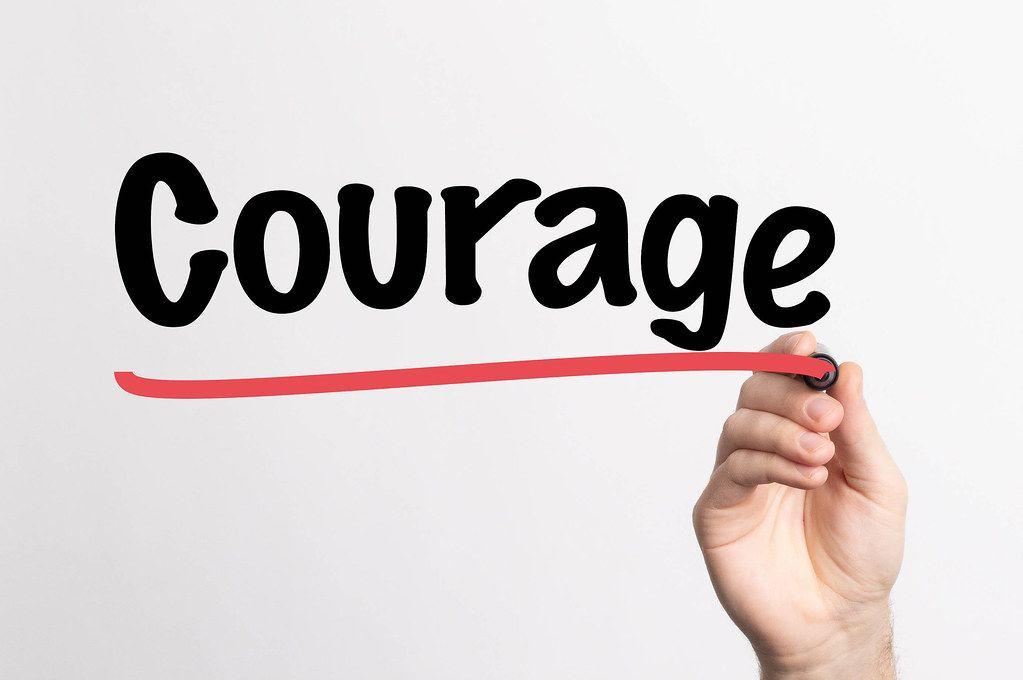 Human hand writing Courage on whiteboard