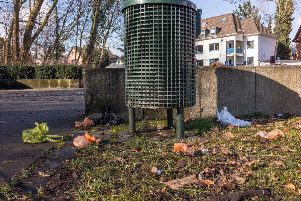 Hundekot-Beutel verstreut um eine Mülltonne