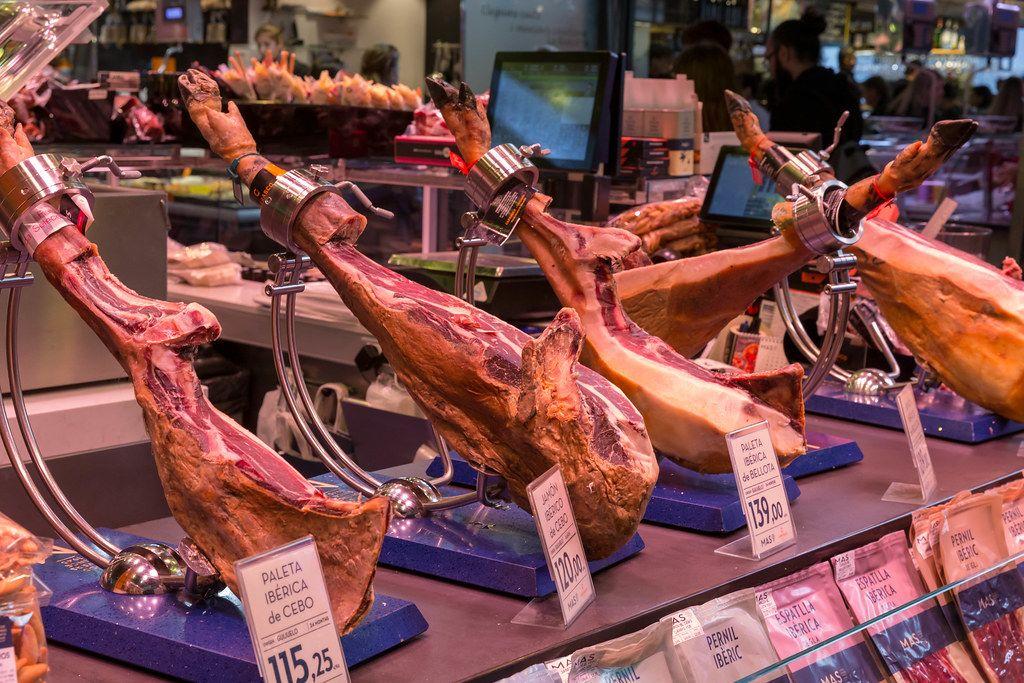 Iberischer Schinken vom Ibérico-Schwein mit Schweinefuß am Fleischstand in der Mercat de la Boqueria an der La Rambla in Barcelona, Spanien