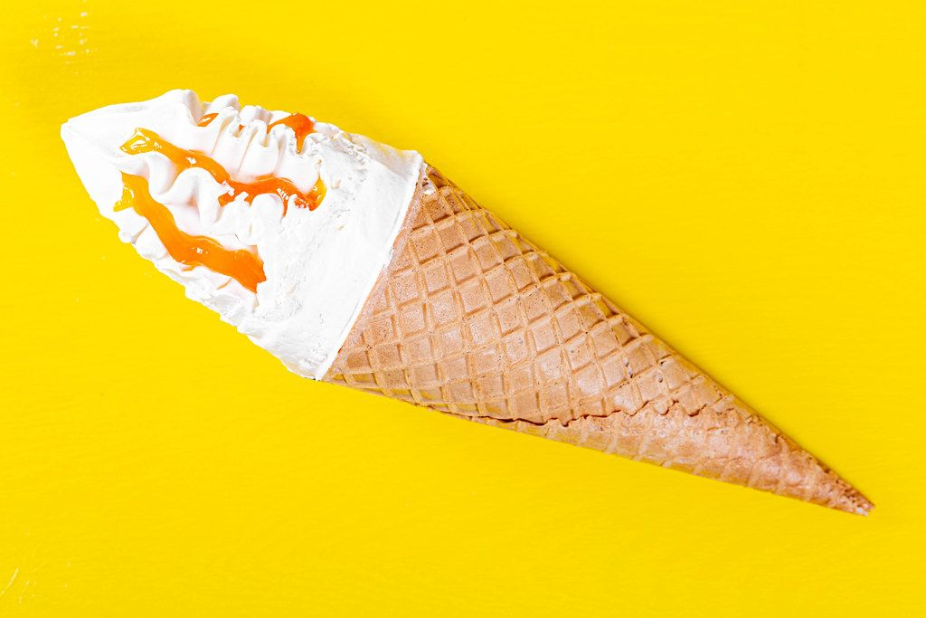 Ice cream in sweet waffle cone with peach jam on yellow background