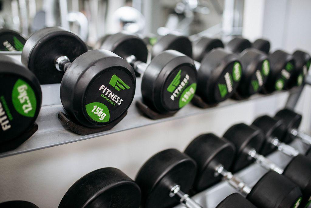 Im Regal sortierte Hanteln für Kraftübungen in Fitnessstudio