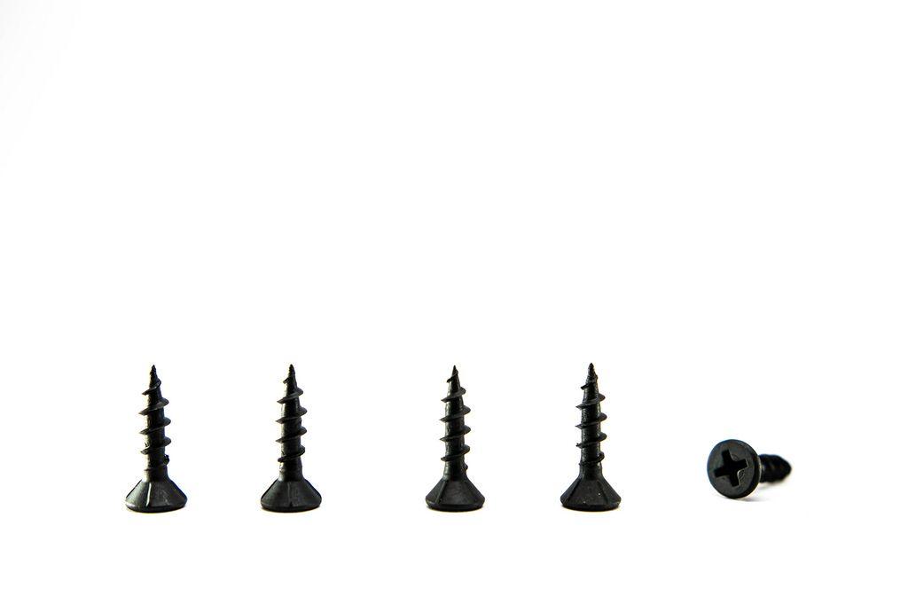 In einer Reihe aufgestellte schwarze kurze Schrauben vor weißem Hintergrund