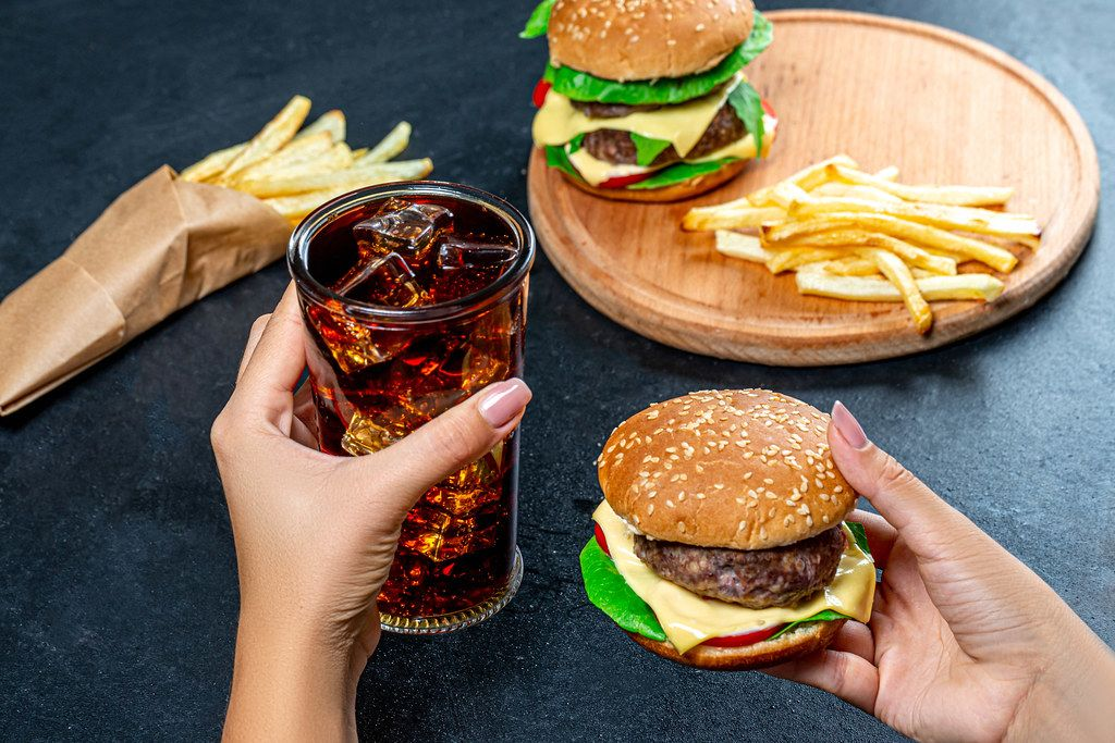 In one hand Burger, in the second the glass with cold Cola. The concept of unhealthy eating (Flip 2019)
